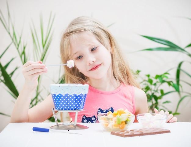 Uma linda garota prepara fondue de chocolate com marshmallow.