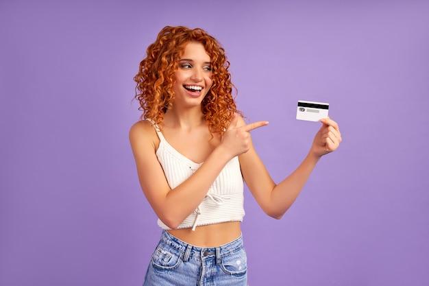 Uma linda garota ruiva com cachos segura um cartão de crédito e aponta o dedo para ele, isolado em uma parede roxa.
