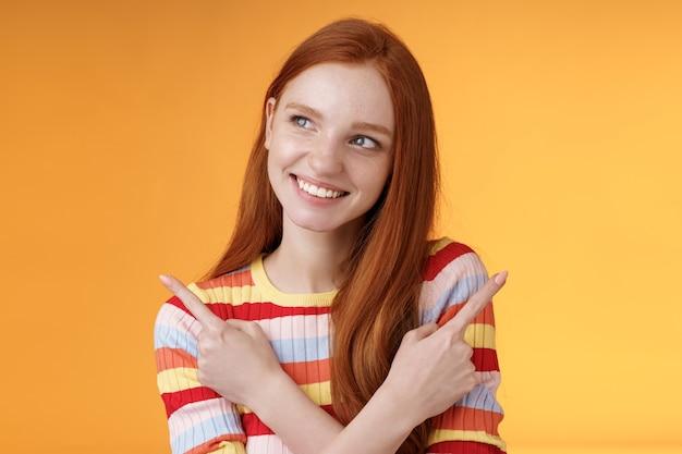 Uma linda garota ruiva sonhadora planejando ir as férias de verão ter diferentes opções escolhendo uma variante olhar intrigado sorrindo satisfeito apontando para o lado esquerdo direito tomando decisão, fundo laranja.