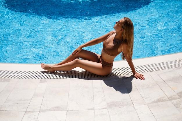 Uma linda garota senta-se sozinha à beira da piscina. ela tem cabelo comprido e um maiô bege. ela é meiga e sexy em um biquíni relaxando na piscina