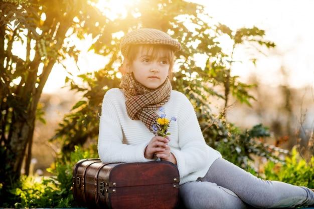 Uma linda garota sentada na plataforma com uma mala vintage ao pôr do sol