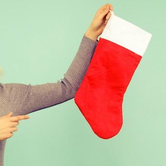 Uma linda garota sexy com um chapéu de ano novo e um vestido cinza aponta o dedo para uma meia de natal. comemoração de natal ou ano novo