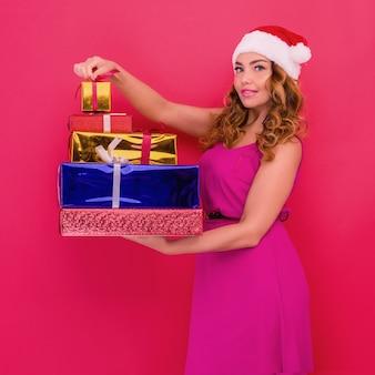 Uma linda garota sexy com um chapéu de ano novo, segurar nos presentes de mãos. comemoração de natal ou ano novo