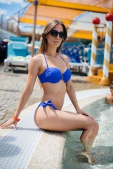 Uma linda garota sexy fica em um dia ensolarado de verão em um parque aquático. recreação, férias e viagens.