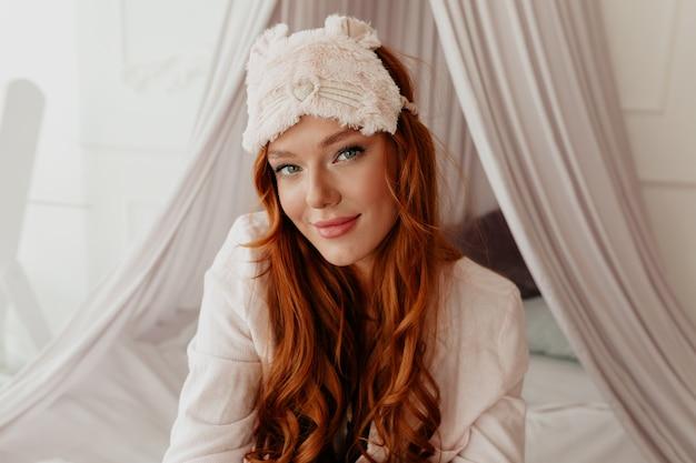 Uma linda garota sonhadora com cabelo ruivo longo ondulado e máscara de dormir olhando para a câmera na cama de manhã