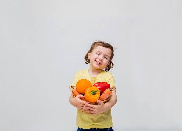 Uma linda garota sorri e segura frutas e legumes. uma menina segura uma cesta de legumes e frutas em um espaço em branco. copie o espaço.