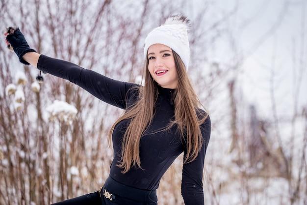 Uma linda garota sorridente com roupas pretas e um chapéu branco de malha no inverno