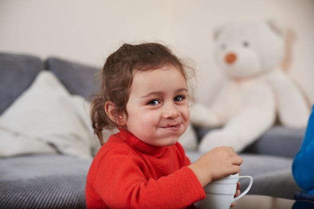 Uma linda garota sorridente se sentindo feliz enquanto bebe um delicioso chocolate com marshmellows