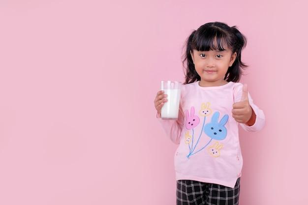 Uma linda garota sorrindo e segurando um copo de leite