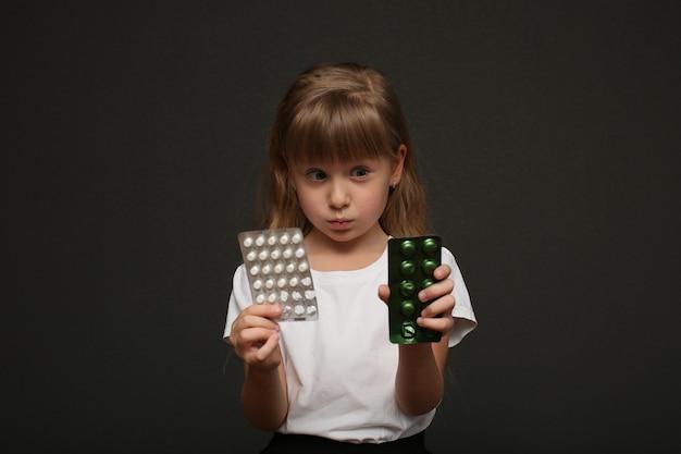 Uma linda garota tem comprimidos nas mãos e olha para eles.