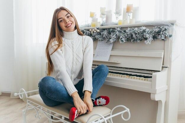 Uma linda garota toca o piano no dia de natal.