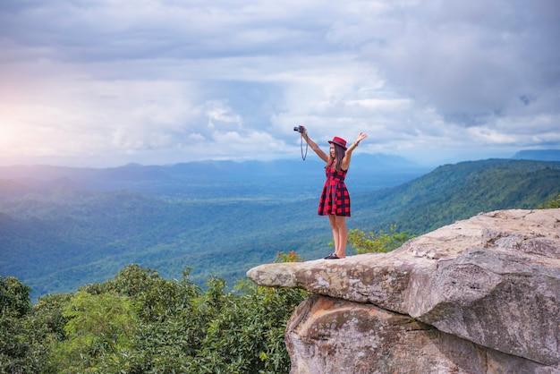 Uma linda garota turística em pé no topo da montanha e tirando uma foto do vale. penhasco sut phaendin, chaiyaphum, tailândia
