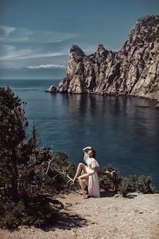 Uma linda garota, uma noiva, em um vestido branco sentada em uma árvore, em um penhasco