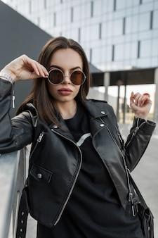 Uma linda garota urbana e bonita com rosto de beleza sexy em óculos de sol redondos da moda com uma elegante jaqueta de couro preta e vestido com bolsa caminha na rua