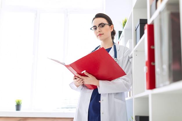 Uma linda garota vestida de branco está de pé perto do abrigo e folheia uma pasta vermelha com documentos.
