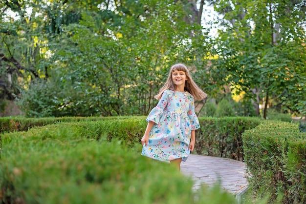 Uma linda garotinha alegre joga em um labirinto de arbustos verdes.