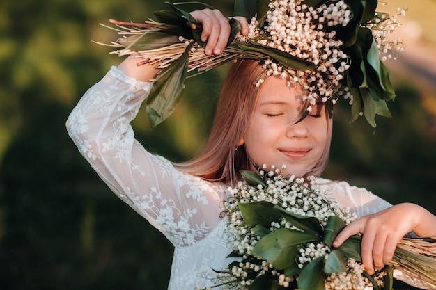 Uma linda garotinha com cabelo comprido em um longo vestido branco, segurando um buquê de flores de lírios do vale