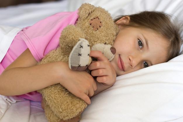 Uma linda garotinha com cabelos loiros e uma camiseta rosa deitada na cama sorrindo e abraçando um ursinho de pelúcia