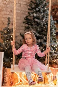 Uma linda garotinha com um elegante vestido rosa senta e rola em um balanço contra o fundo de árvores de natal e luzes em casa