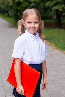 Uma linda garotinha com uma mochila rosa caminha no parque, o conceito de voltar às aulas. uniforme escolar.