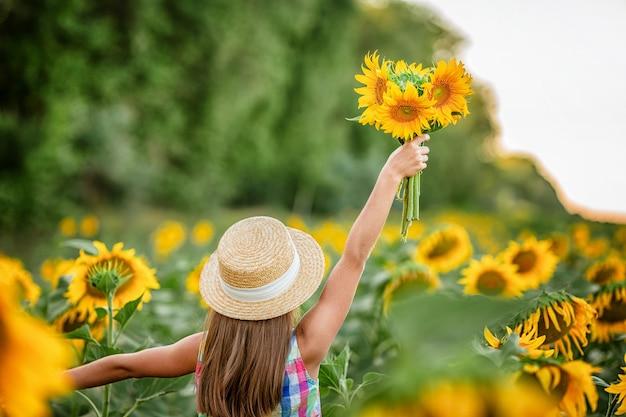 Uma linda garotinha feliz segurando um buquê de flores em um campo de girassóis clima aconchegante de verão