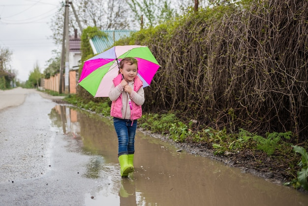Uma linda garotinha percorre poças com um guarda-chuva colorido e botas de borracha verdes. orientação horizontal. ande uma linda garota ao ar livre depois da chuva.
