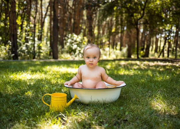 Uma linda garotinha se senta em uma banheira com água e um regador e olha para a câmera na grama verde