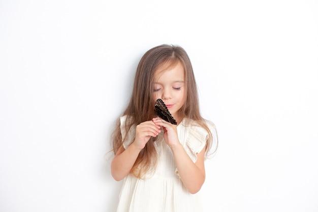 Uma linda garotinha segura uma borboleta morfo viva nas mãos e olha para ela suavemente. emocional