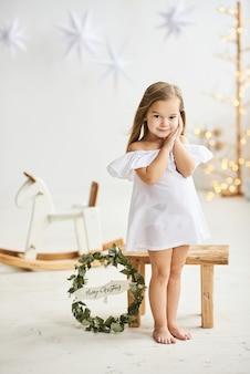 Uma linda garotinha sentada em um banquinho de madeira em um lindo vestido no quarto branco