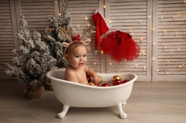 Uma linda garotinha tomando banho em uma banheira com brinquedos vermelhos e dourados para a árvore de natal. a garota está feliz