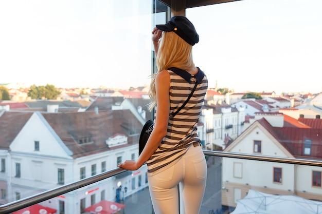 Uma linda jovem apreciando a vista panorâmica da cidade velha da cabine de um elevador panorâmico em hrodna, bielorrússia.
