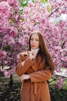 Uma linda jovem caminha num dia de primavera em um pomar de florescência. estilo de vida, recreação.