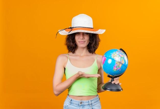 Uma linda jovem com cabelo curto em um top verde recortado usando chapéu de sol, sorrindo e mostrando um globo