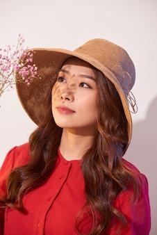 Uma linda jovem com um vestido de verão e chapéu de palha posando enquanto segura um buquê de flores