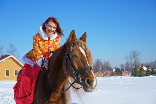 Uma linda jovem com uma jaqueta vermelho-amarela quente monta um cavalo em um dia gelado e ensolarado de inverno. pratica esportes equestres na temporada de inverno