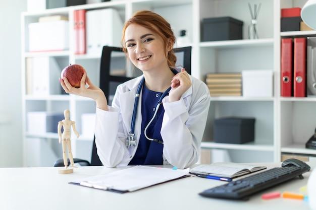 Uma linda jovem com uma túnica branca está sentado em uma mesa no escritório e está segurando uma maçã na mão.