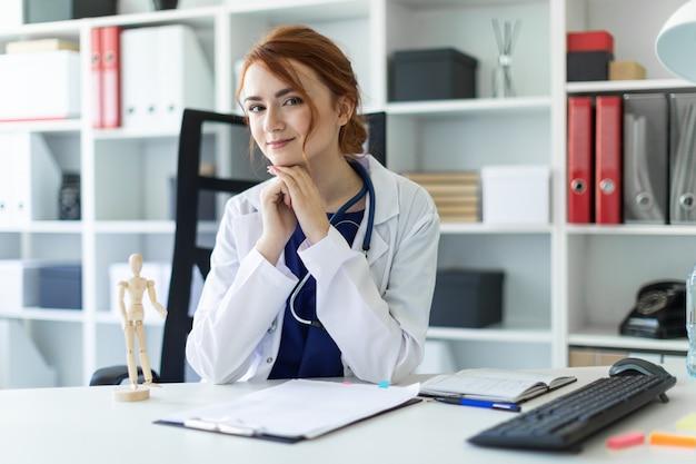 Uma linda jovem com uma túnica branca está sentado em uma mesa no escritório.