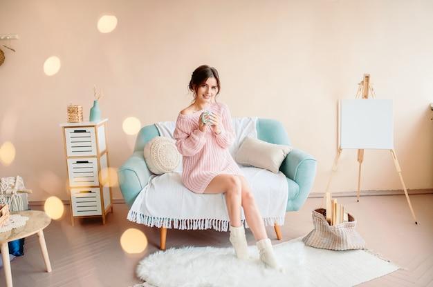 Uma linda jovem de aparência europeia senta-se em um ambiente doméstico acolhedor com uma caneca de contusões na mão