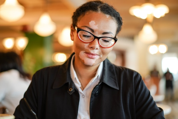 Uma linda jovem de etnia africana com vitiligo sentado em um restaurante