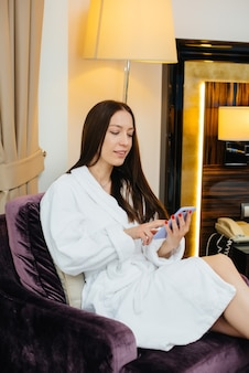 Uma linda jovem de jaleco branco está falando ao telefone em seu quarto de hotel