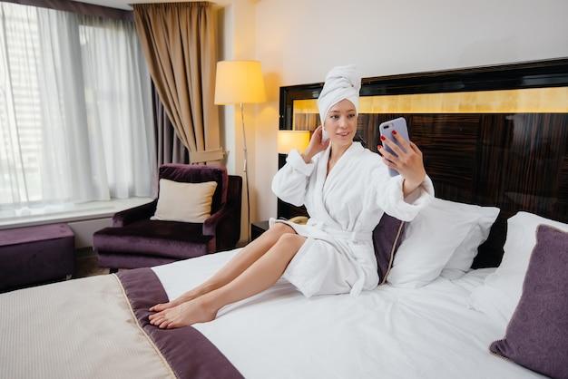 Uma linda jovem de jaleco branco tira uma selfie com o telefone no quarto de hotel
