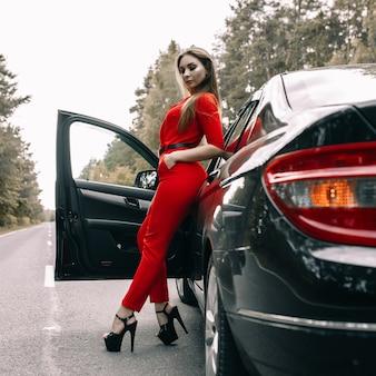 Uma linda jovem de macacão vermelho está parada ao lado de um carro preto em uma estrada vazia na floresta