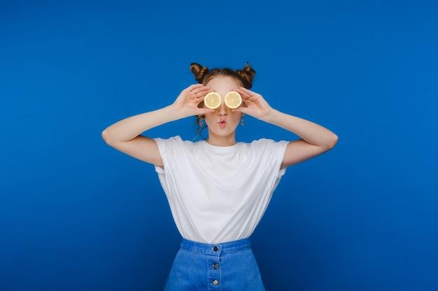 Uma linda jovem de pé sobre um fundo azul tem limões nas mãos e cobre os olhos com eles.
