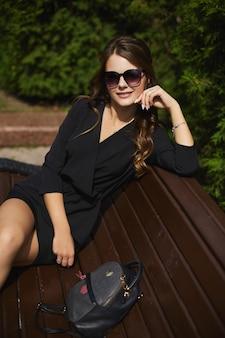 Uma linda jovem de vestido preto e óculos escuros sentada no banco na rua da cidade ...