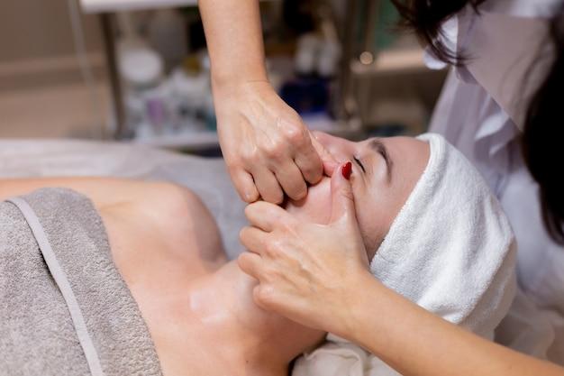 Uma linda jovem deita-se na mesa da esteticista e recebe procedimentos, uma leve massagem facial.