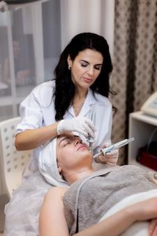Uma linda jovem deita-se na mesa da esteticista e recebe procedimentos