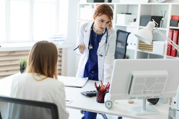 Uma linda jovem em um manto branco está de pé perto de uma mesa de computador no escritório e se comunicando com o interlocuto