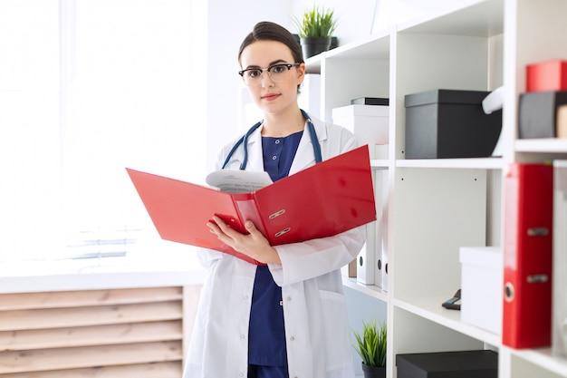 Uma linda jovem em um manto branco está de pé perto do abrigo e folheia uma pasta vermelha com documentos.