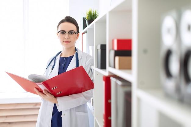 Uma linda jovem em um manto branco está de pé perto do abrigo e folheia uma pasta vermelha com documentos