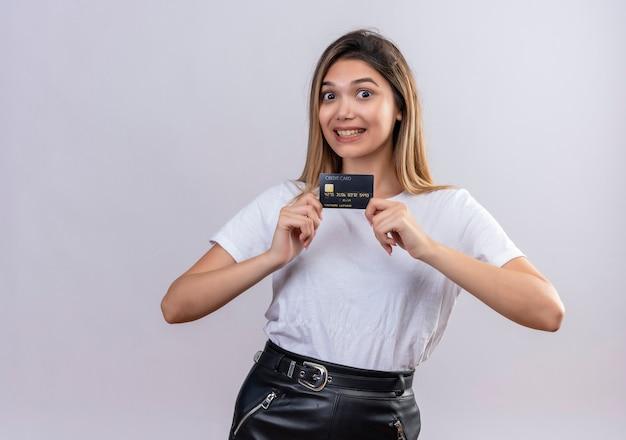Uma linda jovem em uma camiseta branca sorrindo enquanto mostra o cartão de crédito em uma parede branca